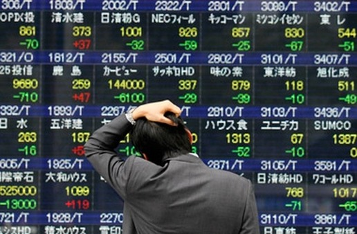 A man looks at a trading board in Tokyo. (Photo: AP)