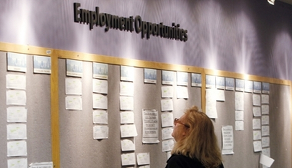 An unemployed worker examines a job posting board. (Photo: AP)