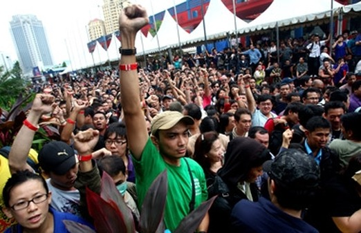Indonesians on Black Friday raised their fists to show 'priority' wristbands as they jammed a Jakarta shopping mall to buy the first BlackBerry Bold 9790s. (Photo: AP)