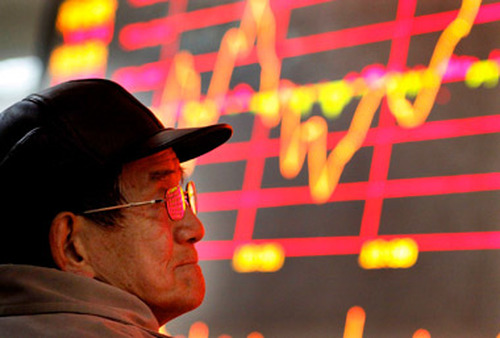 A man looks at a stock price monitor at a private securities firm in Shanghai. (Photo: AP)