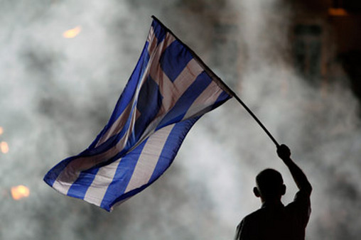 A New Democracy supporter waved a Greek flag during a rally in Athens on Friday. (Photo: AP)