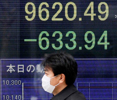A man in front of a Nikkei stock board shortly after the 2011 earthquake. (Photo: AP)