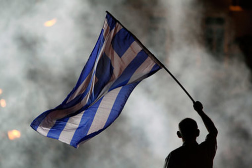 A New Democracy supporter waved a Greek flag during a rally in Athens before the election in June. (Photo: AP)