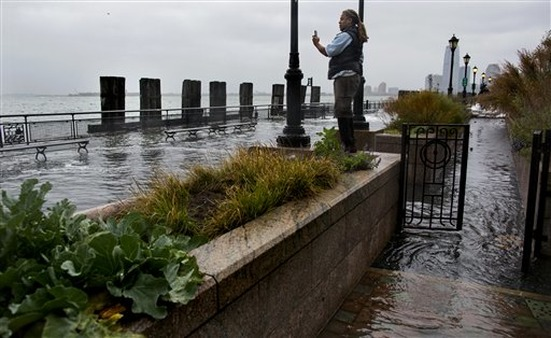 Water washes over the sea wall near high tide at Battery Park in New York on Monday. (Photo: AP)