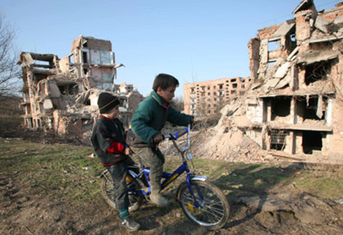 Chechen children ride a bicycle near destroyed houses in Grozny, Chechnya, in 2007. (Photo: AP)