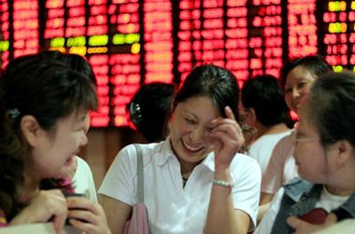 Women in front of a stock board in Shanghai. (Photo: AP)