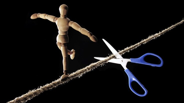 Acrobat on a tight rope, with scissors about to cut the rope