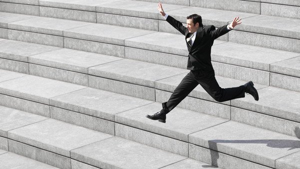 Businessman leaping down stairs