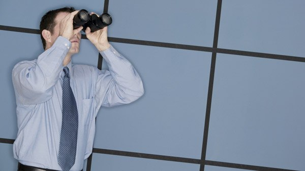 stock photo of man looking out with binoculars