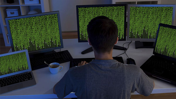 A shadowy figure in front of a computer screen (Image: Shutterstock)
