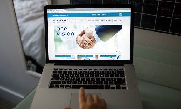 The Envision Healthcare Corp. website is displayed on an Apple Inc. laptop computer in an arranged