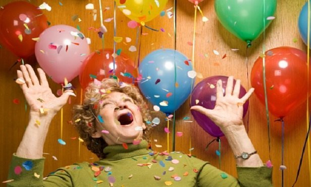 A very happy woman, with confetti and balloons (Image: Thinkstock)