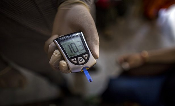 A Public Health Foundation of India worker shows the blood glucose level of a patient during a free door-to-door screening program funded by Eli Lilly & Co. at a home in the farming village of Thana kalan, Haryana, India, on Thursday, July 13, 2017. Global pharmaceutical companies, from Indianapolis-based Eli Lilly to Switzerland's Novartis AG, are heading into smaller cities and rural areas to learn about the health-care needs of about 70 percent of the population. These remote regions of the developing world are the final frontier for the international drug industry. Photographer: Prashanth Vishwanathan/Bloomberg