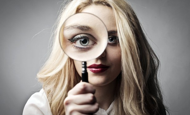 Woman with magnifying glass: Regulation vs. oversight