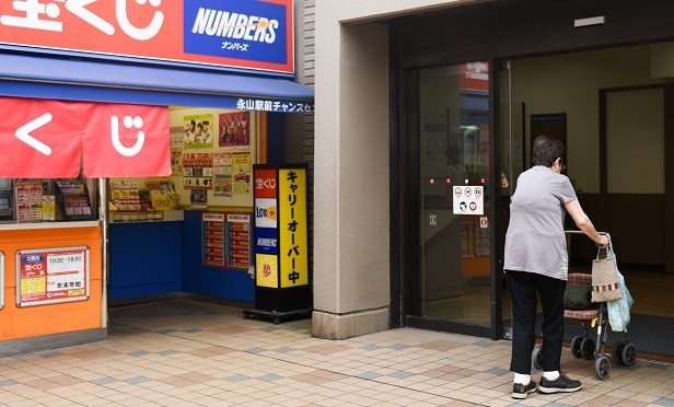 A woman walks past a lottery store in Tama City, Tokyo, Japan, on Tuesday, Aug. 28, 2018. As Japanese society ages and the government cuts social welfare spending, older women are bracing for the impact; they are under financial strain because they are less likely to have jobs to supplement their benefits. Photographer: Noriko Hayashi/Bloomberg