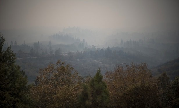 Haze fills a valley outside of Paradise, California, U.S., on Tuesday, Nov. 13, 2018. The Camp Fire north of Sacramento has now killed at least 42 people, injured three firefighters and destroyed 6,500 homes, CalFire said Tuesday morning. Photographer: David Paul Morris/Bloomberg