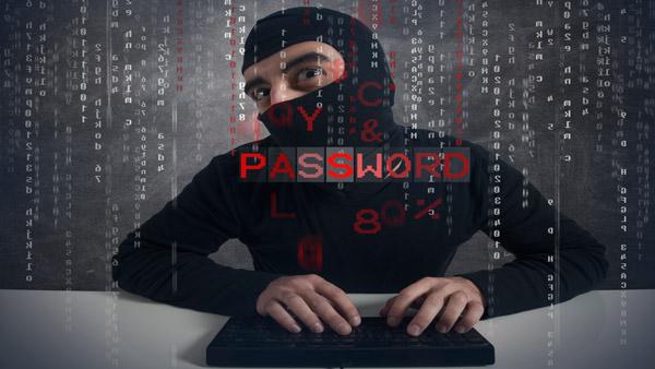 Masked criminal using computer.