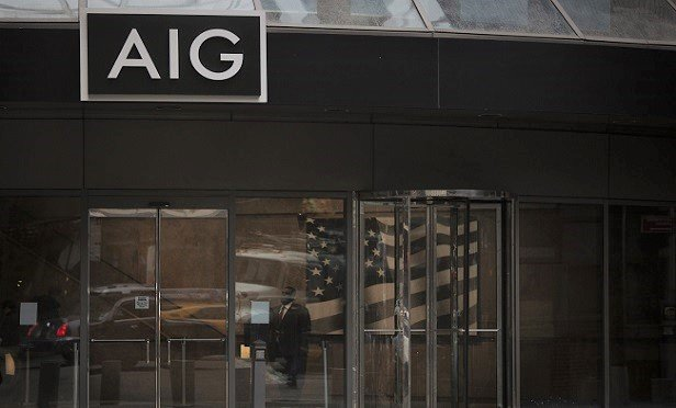 A security guard stands inside the American International Group Inc. (AIG) headquarters office in New York, U.S., on Tuesday, Jan. 29, 2016. American International Group Inc., the insurer being pressured by activist investor Carl Icahn to divest assets, had the outlook on its credit rating changed to negative from stable by Standard & Poor's after announcing plans to sell a stake in mortgage insurer United Guaranty Corp. Photographer: Victor J. Blue/Bloomberg