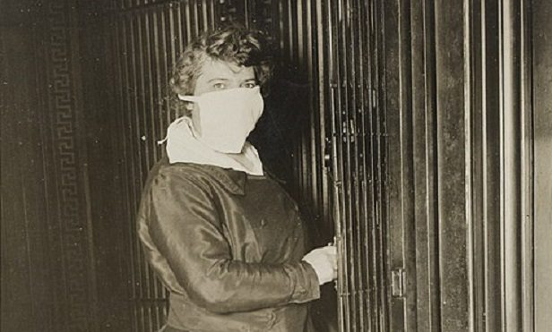 A woman in a surgical mask, in an old photo.