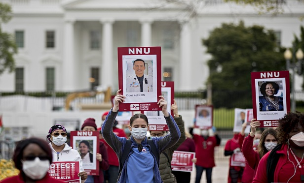 Members of National Nurses Untied (NNU) wear protective masks while demonstrating outside the White House in Washington, D.C., U.S., on Tuesday, April 21, 2020. NNU, the nations' largest union of registered nurses in the country representing 155,000 RNs, is demanding the White House helps to ensure healthcare workers have adequate personal protective equipment (PPE) while working with coronavirus patients. Photographer: Andrew Harrer/Bloomberg