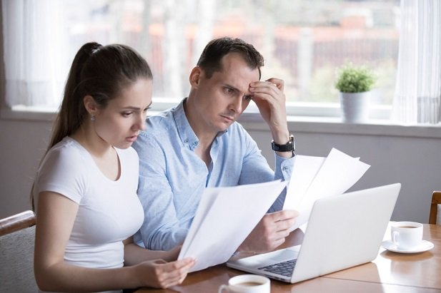 An unhappy man and woman looking at pieces of paper
