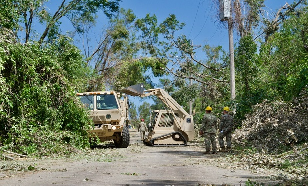 Iowa National Guard soldiers remove tree limbs and other debris from power lines and roadways, Aug. 14, 2020, after a derecho hit the eastern part of the state. In the first three days of response efforts, the soldiers moved nearly 2.25 million pounds of debris and cleared the equivalent of 68 city blocks.