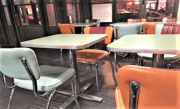 Empty tables and chairs in a restaurant, in New York City