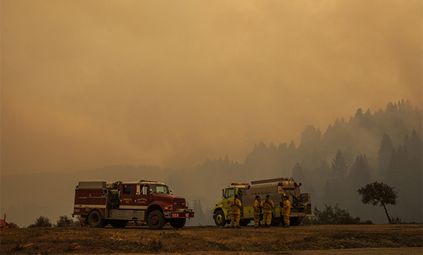 Firefighters, two trucks and smoke in Sonoma County on Aug. 22, 2020, in photo taken by Bloomberg