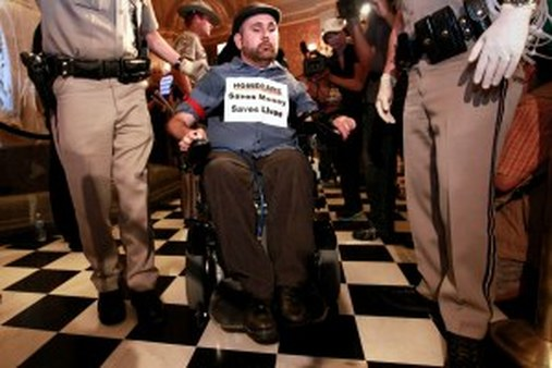 A wheelchair bound demonstrator is removed from the rotunda of the California Capitol in June, during a protest against proposed state home care services budget cuts. (AP Photo/Rich Pedroncelli)