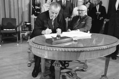 President Lyndon Johnson uses the last of many pens to complete signing the Medicare bill into law in 1965. (AP Photo)