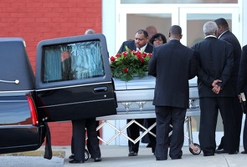 Pallbearers place a coffin with the body of Kansas City Chiefs player Jovan Belcher into a hearse. Belcher shot his girlfriend Saturday morning before turning the gun on himself. (AP Photo/Ed Zurga)