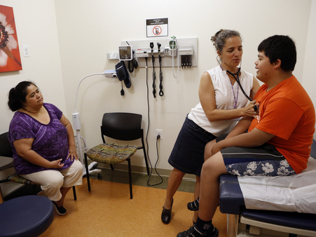 In Washington, D.C., Dr. Cheryl Focht of Mary's Center performs a checkup of Jayson Gonzalez, 16, while his mother, Elizabeth Lopez, looks on. (Heather Rousseau/NPR)