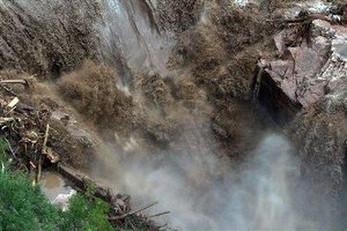 A raging waterfall destroys a bridge along Highway 34 toward Estes Park, Colo. (AP Photo/Colorado Heli-Ops, Dennis Pierce)