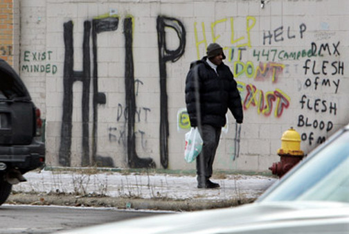 Man passes by graffiti in Detroit. (Photo Credit:
