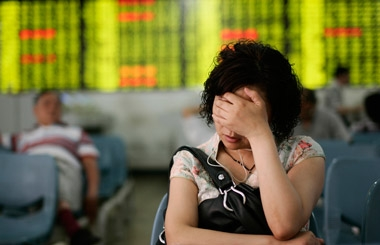 An investor in front of a stock board in Shanghai. (Photo: AP)