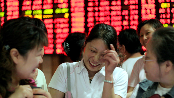 Chinese investors laughing in front of stock board. (Photo: AP)