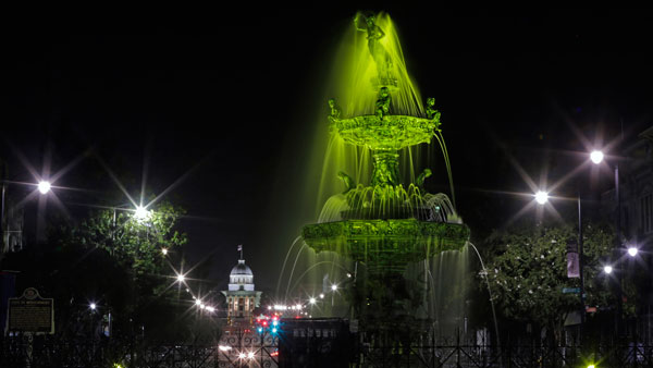 The Alabama Capitol sits in the background as the Court Square Fountain in downtown Montgomery is lit green. (Photo: AP)