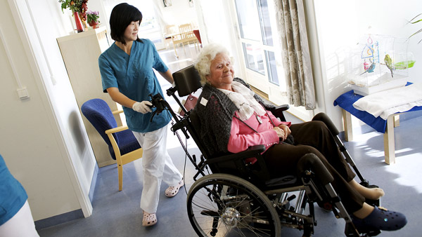 Attendant helps patient in nursing home. (Photo: AP)