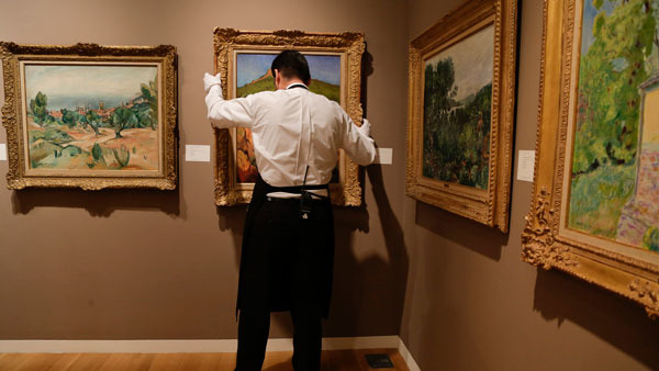 Attendant prepares art during a preview exhibition for a recent Sotheby auction. (Photo: AP)