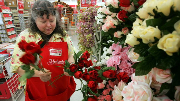 A sales associate works on a flower display at Michaels arts and crafts store. (Photo: AP)