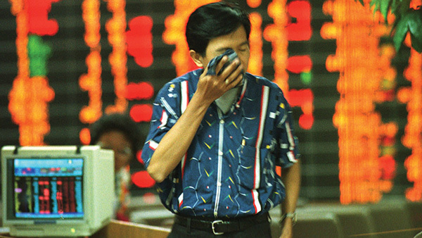 A Thai investor wipes his face while walking out a trading room at the Stock Exchange of Thailand in Bangkok Tuesday, Oct. 28, 1997. (Photo: AP/Thaksina Khaikaew)