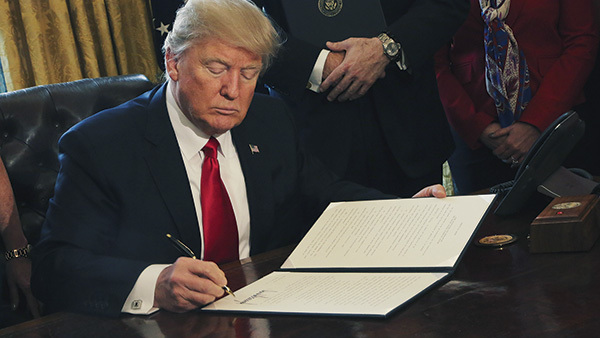 Pres. Donald Trump signs an executive order in the Oval Office. (Photo: AP)