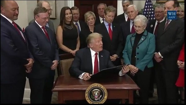 President Donald Trump signs the health executive order as members of Congress, cabinet secretaries and others watch. (Photo: White House)