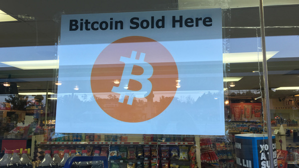 Advertisement for Bitcoin in window of a minimart's store front. (Photo: John Disney/ALM)